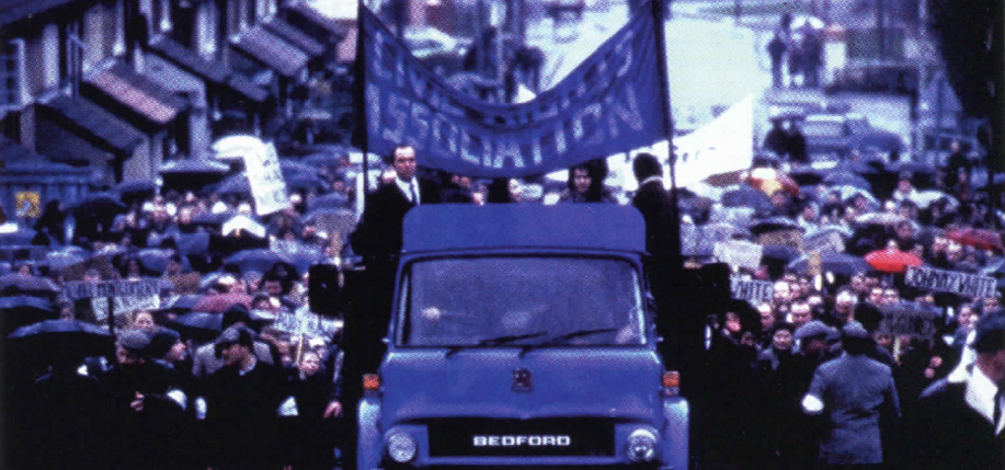 James Nesbitt (on truck) as politician Ivan Cooper leads marchers before violence erupts in Bloody Sunday.