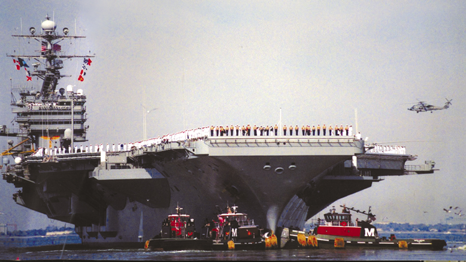 Two of the most modern Moran tugs guide the U.S.S. Roosevelt from Norfolk harbor following September 11, 2001.