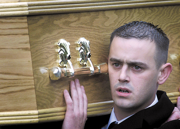 John Lawlor, brother of murdered Catholic teenager Gerard Lawlor, carries his coffin from his North Belfast home. Lawlor was shot dead by an Ulster Freedom Fighter (UFF) gunman.