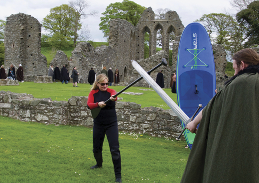 Pam brandishing her paddle, breaks into mock swordplay with a Game of Thrones fan at Inch Abbey.