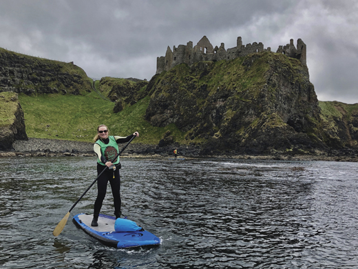 Pam paddles by Dunluce Castle during a trip along the cliffs of the Causeway Coast.